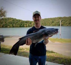 A man holding a blue catfish with a lake in the background.