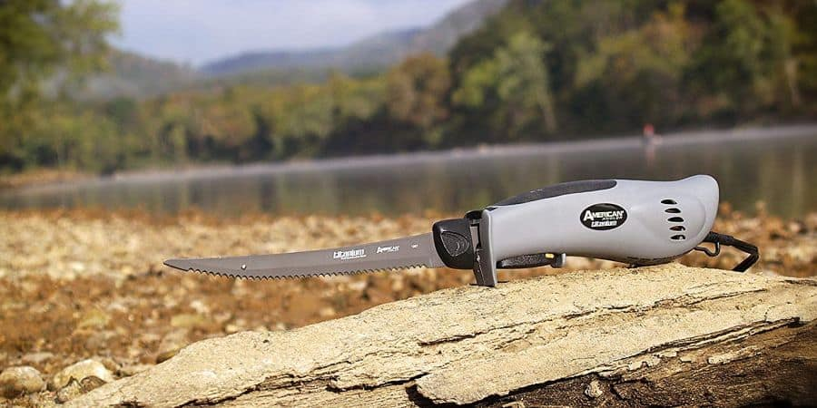 American Angler PRO electric fillet knife sitting on a wooden log with river in background.