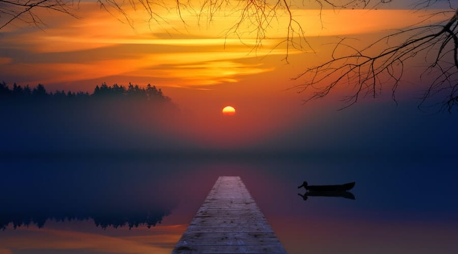 A picture of a fishing dock at sunset with a boat in the water in the background.