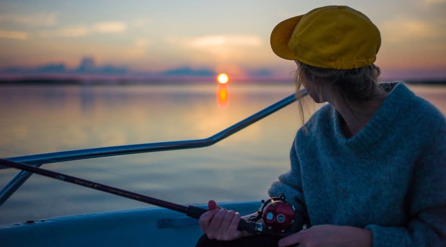 A person holding a fishing rod on a boat with the sunset beaming off the water in the background.