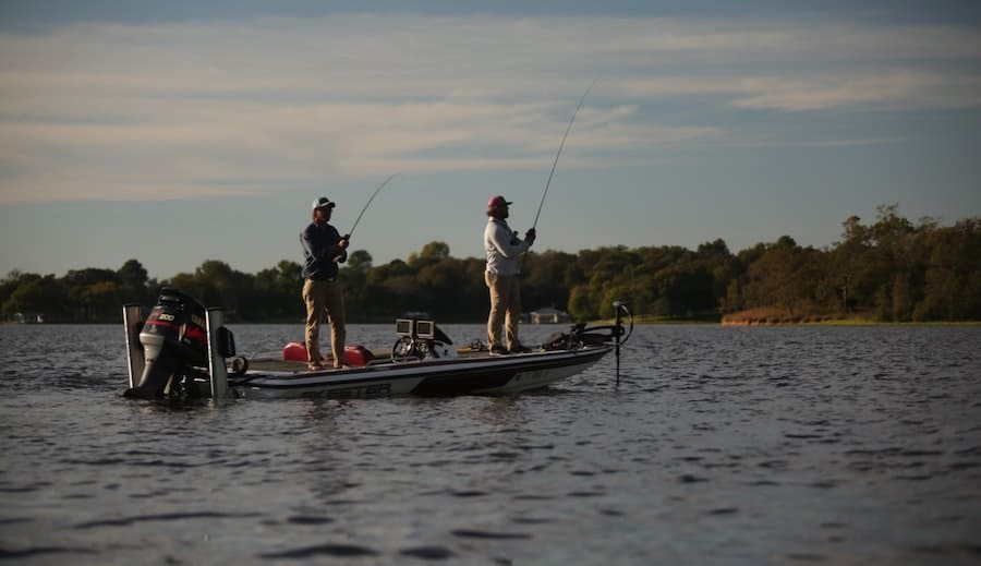 Two anglers fishing on a boat with water and trees in the background.