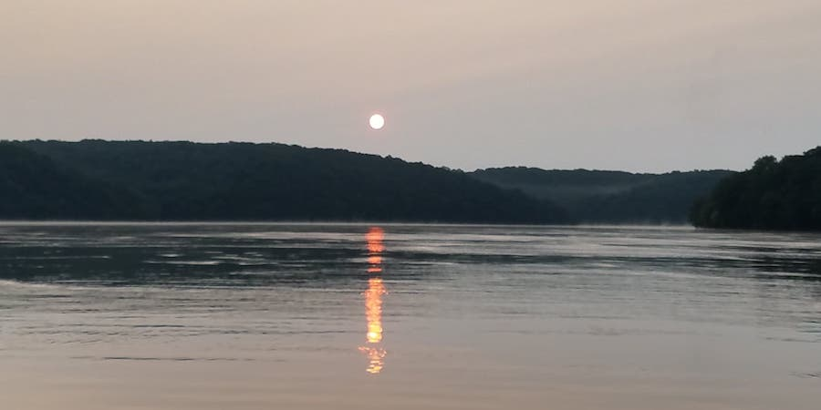 A photo of a lake at the break of dawn with the sun rising in the background.
