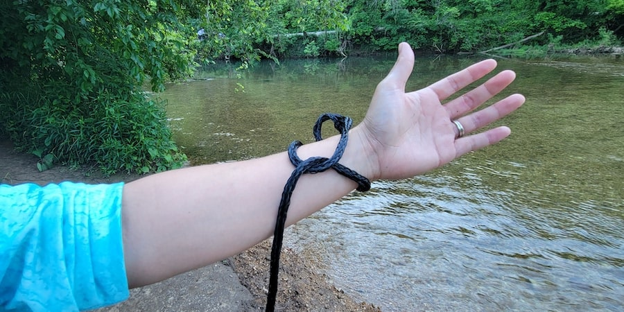 The handline of a cast net secured onto an arm with a river in the background