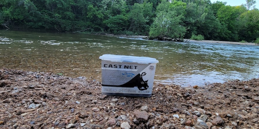 The box of a throw net with a river in the background