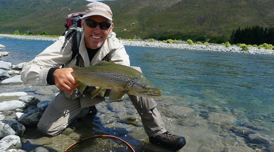 A man holding a fish with a body of water in the background.