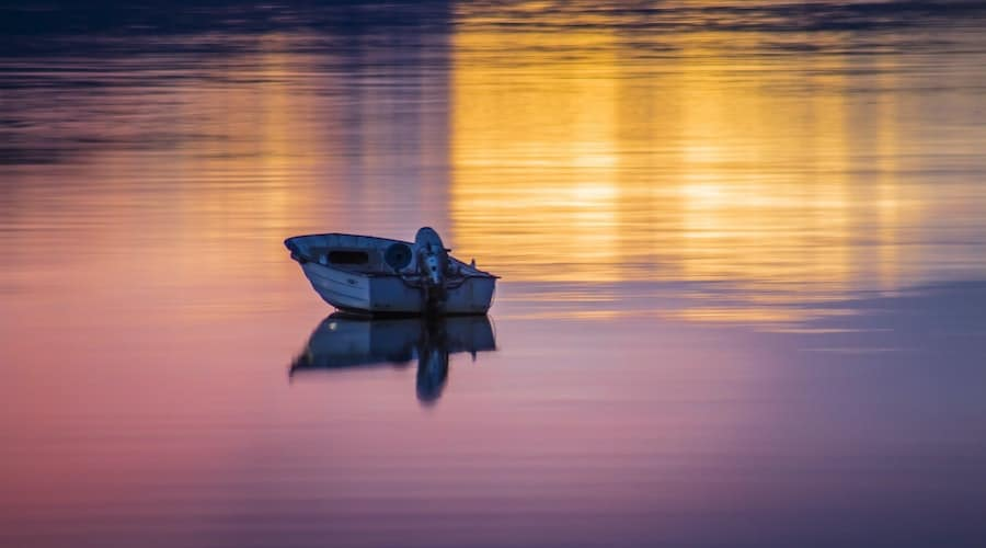 A fishing boat on the water at before night.