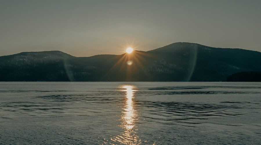 The sun rising above a mountain and a lake.