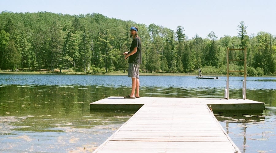 A person fishing at the end of a dock with a lake and trees in the background.
