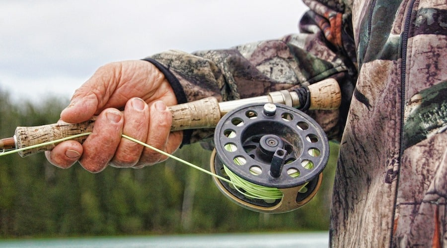 A person holding a fly fishing rod with trees in the background.