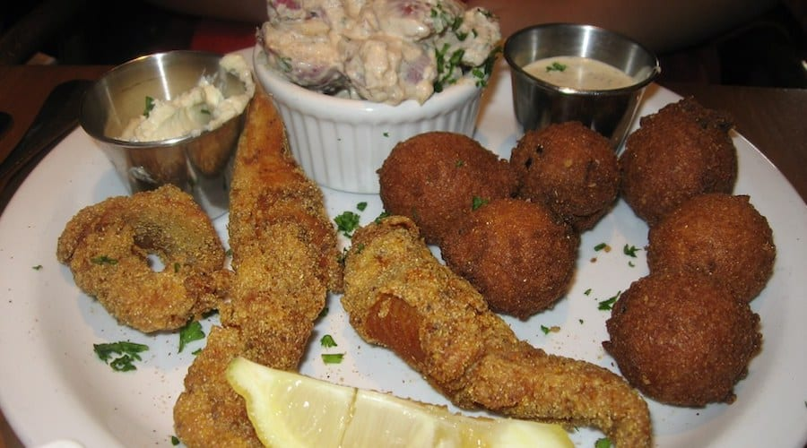 Cornmeal fried catfish served with hush puppies, dipping sauce, and a lemon on the plate.