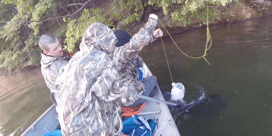 A group of anglers catching catfish on a lake using a limb line.