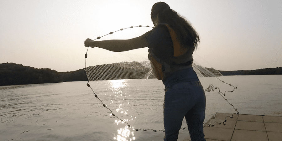 Me throwing a cast net to catch live bait for catfishing with the lake in the background.