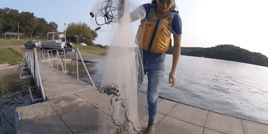 A woman holding a cast net on a dock with a lake in the background