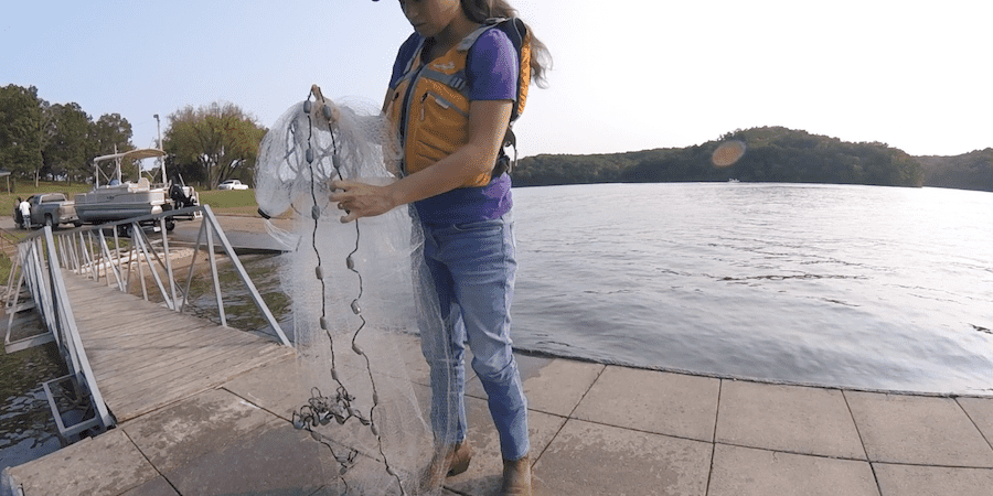 A woman placing the lead line behind her thumb with a lake in the background
