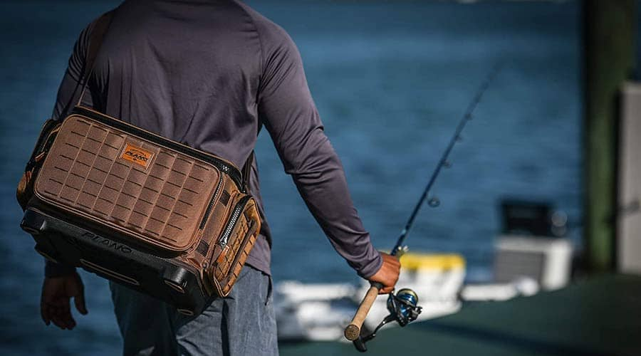 A man holding a fishing rod and a tackle bag with water in the background.