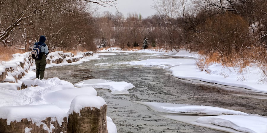 A person fishing in the winter with an icy stream in the background.
