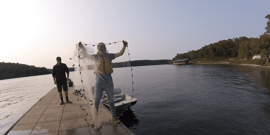 A woman grabbing a lead line with a lake in the background