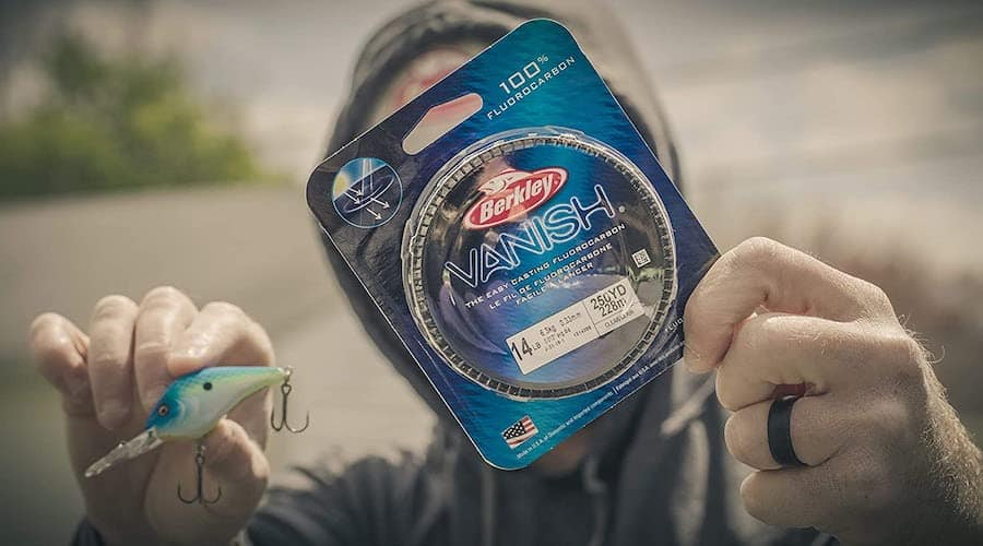A person holding Berkley's Vanish fluorocarbon fishing line and a lure.